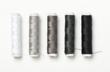 Flat lay top down view on white, grey anf black sewing threads row on white wooden table