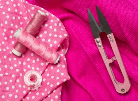 Pink colored flat lay top view sewing tools with thread and scissors on pink fabric textile background
