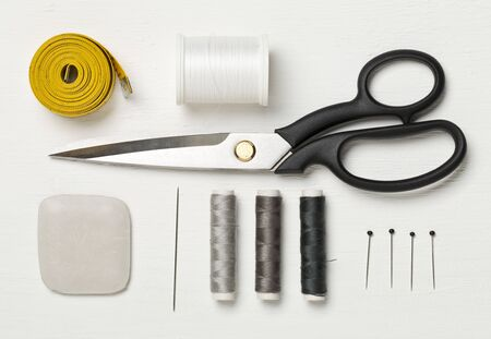 Flat lay top view tools with measuring tape, chalk, thread, needles and scissors on white wooden table