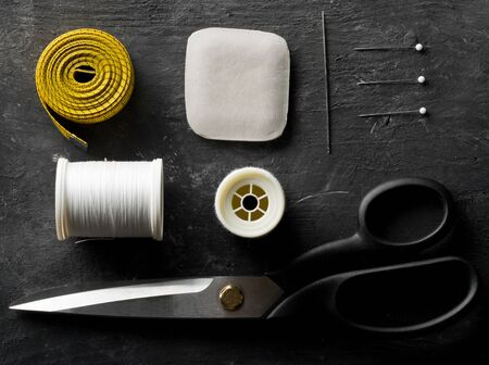 Flat lay top view sewing tools with measuring tape, chalk, thread, needles and scissors on black dark wooden table Stok Fotoğraf