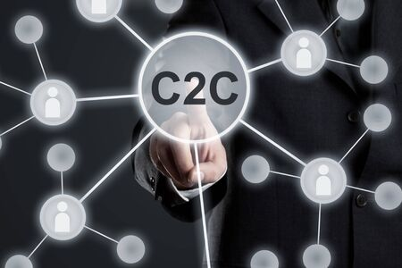 Executive businessman in suit touching C2C button in network with people icons on virtual touch screen - consumer to consumer network concept Stockfoto