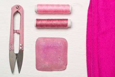 Pink colored flat lay top view sewing tools with texile fabric, chalk, thread and scissors on white wooden table Stok Fotoğraf
