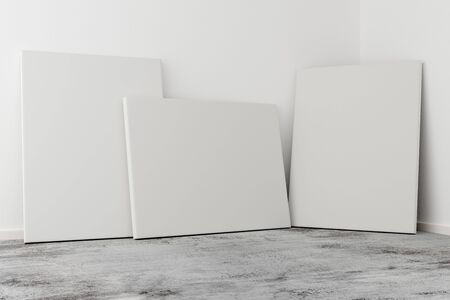 Multiple empty picture frames canvases leaning against white wall in bright room with grey concrete floor with copy space - portfolio, gallery or artwork template mock up - 3D illustration