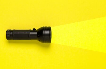 Flashlight or torch lighting up yellow background - minimal concept for internet search or direction finding
