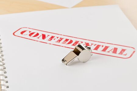 Chrome whistle on documents with confidential top secret information on wooden office desk - whistleblower concept, selective focus
