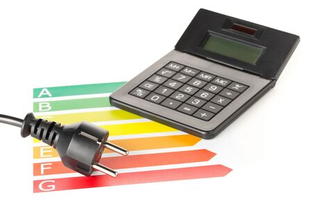 European energy classification labels with power cord, plug and calculator on white background - energy saving or power consumption concept