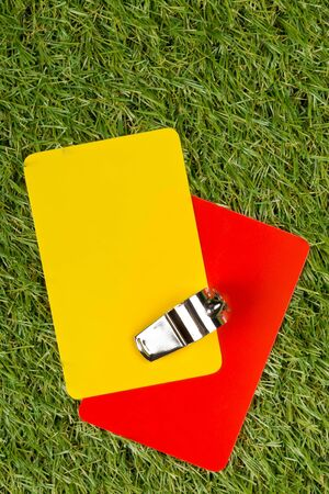Soccer sports referee yellow and red cards with chrome whistle on grass background - penalty, foul or sports concept, top view flat lay from above Archivio Fotografico