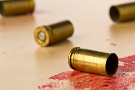 Empty, fired, blood covered 9mm bullet casings on wooden floor background at CSI crime scene investigation - police, evidence or forensic investigation concept, selective focus