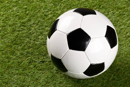 Single soccer ball on green grass lawn background with copy space - selective focus