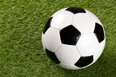 Singolo pallone da calcio sul fondo del prato inglese dell'erba verde con lo spazio della copia - fuoco selettivo