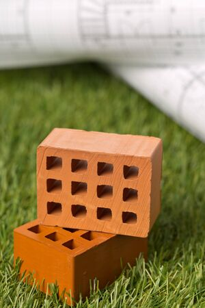 Architectural blueprints with miniature bricks on green grass lawn background - house building or buying concept, selective focus