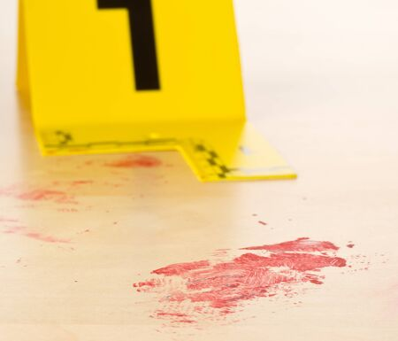 Crime scene investigation CSI evidence marker with blood spot on wooden floor background at crime scene - police, evidence or forensic investigation concept