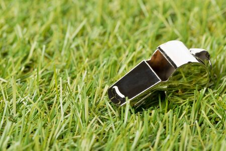 Soccer sports silver chrome whistle on grass background - penalty, foul or sports concept, selective focus