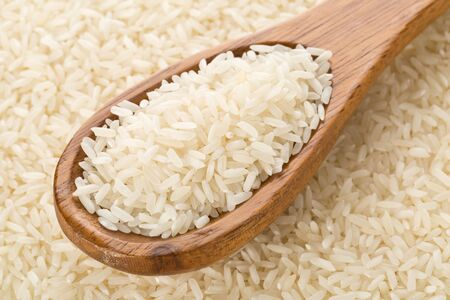 Heap of white uncooked, raw long grain rice in wooden spoon on rice kernels background - selective focus
