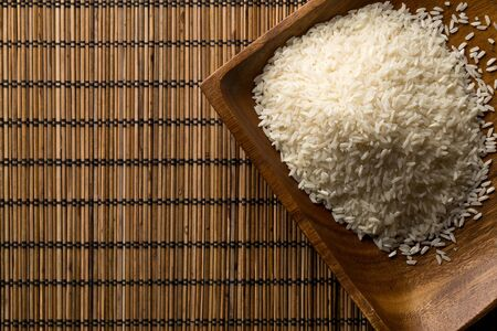 White uncooked, raw long grain rice in wooden bowl on bamboo mat with copy space top view flat lay from above - selective focus Stock fotó