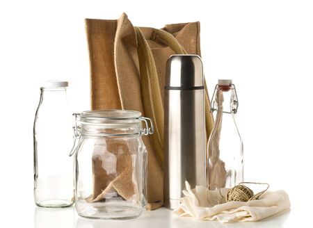 Zero waste or waste free shopping utensils with burlap bag, glass bottles and cotton bag over white background - waste reduction eco lifestyle or bulk buy grocery concept