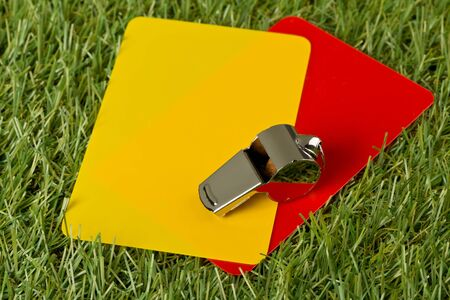 Soccer sports referee yellow and red cards with chrome whistle on grass background - penalty, foul or sports concept Foto de archivo