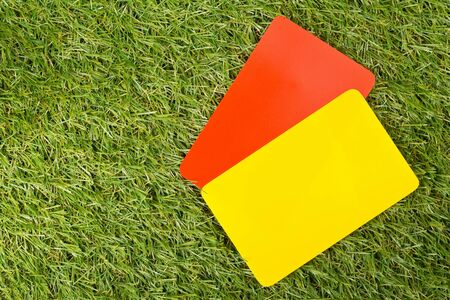 Soccer sports referee yellow and red cards on grass background - penalty, foul or sports concept, top view flat lay from above