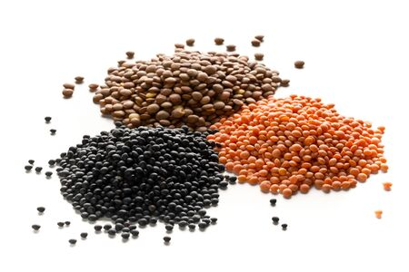 Different assorted lentils mix with red, brown and black beluga lentils on white background - selective focus
