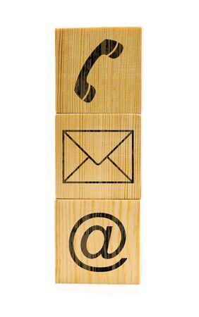 白い背景に積み重ねられた茶色の木製の立方体に電話、電子メール、封筒のアイコンを使用してシンボルにお問い合わせください