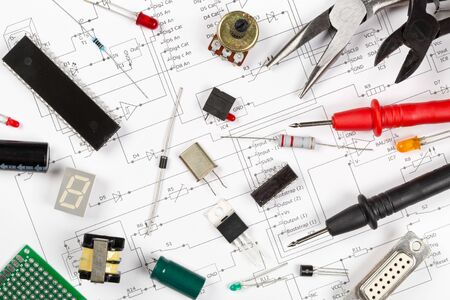 Different electronic parts or components on pcb wiring scheme background with resistors, capacitors, diode and ic chips, flat lay top view from above