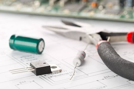 Transistor, resistor and capacitor electronic parts or components with pliers in front of pcb board with pcb wiring diagram - electronic device repair concept, selective focus