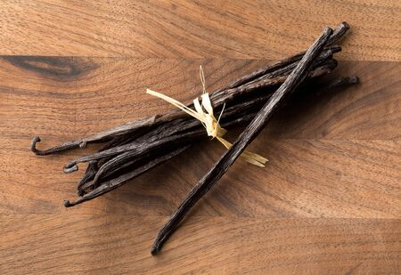 Bundle of tied, dried bourbon vanilla beans or pods on brown wooden cutting board flat lay top view from above