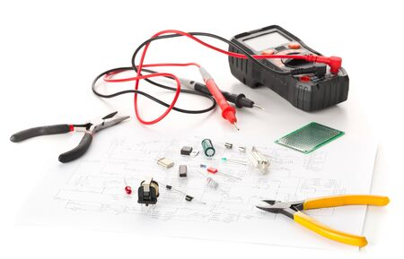 Different electronic parts or components, measurement tool and pliers on white background with pcb wiring diagram, resistors, capacitors, diode and ic chips, selective focus Banco de Imagens