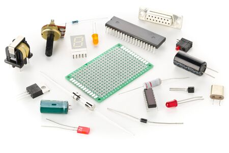 Different electronic parts or components on white background with resistors, capacitors, diode and ic chips, selective focus Foto de archivo