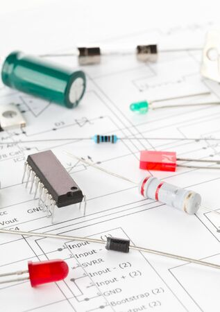 Macro of different electronic parts or components on pcb wiring diagram background with resistors, capacitors, diode and ic chips, selective focus