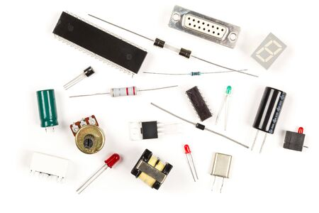 Different electronic parts or components on white background with resistors, capacitors, diode and ic chips, flat lay top view from above