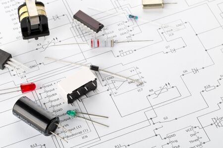 Different electronic parts or components on pcb wiring diagram background with resistors, capacitors, diode and ic chips, with copy space, selective focus