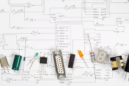 Different electronic parts or components on pcb wiring scheme background with resistors, capacitors, diode and ic chips, flat lay top view from above with copy space