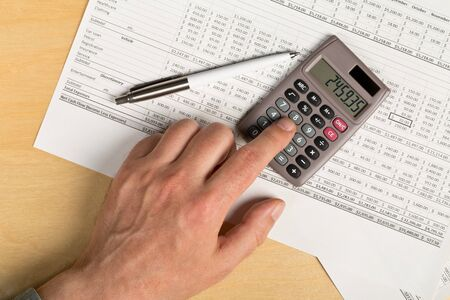 Man using pocket calculator with pen on financial analysis sheet background on wooden office desk with copy space - tax, finance or accounting concept, top view flat lay from above