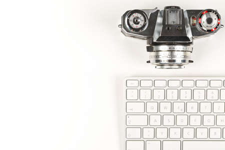Retro analog SLR camera next to computer keyboard on white background, digital photography or image processing concept, flat lay top view from above with copy space