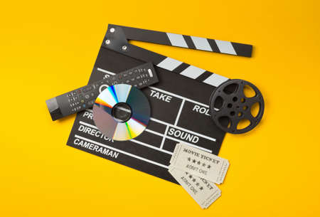 Single, black, open movie clapper or clapper-board with dvd movie disc, film reel, remote control and movie theater tickets on yellow or orange background - digital movie, home cinema or movie night concept Stockfoto