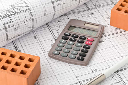 Calculator with pen and bricks on architectural house building blueprint plan background, real estate or house building costs concept 免版税图像