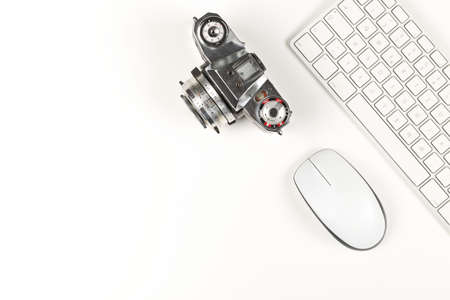Retro analog SLR camera next to computer keyboard and mouse on white background, digital photography or image processing concept, flat lay top view from above with copy space Imagens