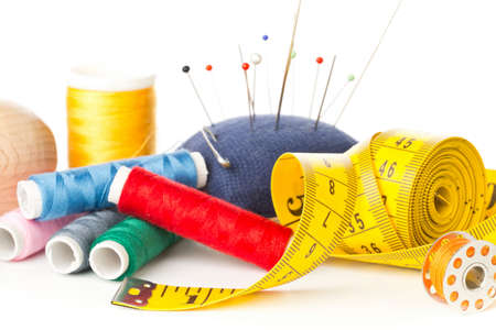 Close up of collection of sewing tools with yarn, needles, scissors and tape measure over white background with selective focus