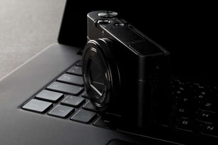 Modern digital camera on laptop keyboard on black desk in office, digital photography or image processing concept, selective focus Imagens