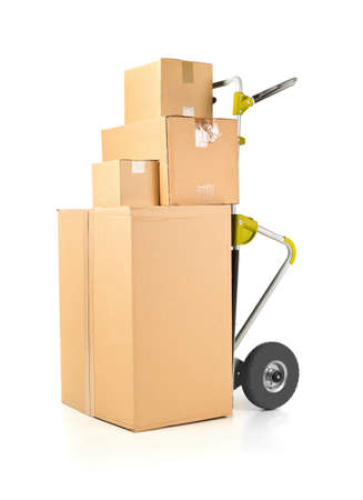 Heap or stack of brown carton transport boxes with barrow over white background, delivery, freight or transportation industry concept Banco de Imagens