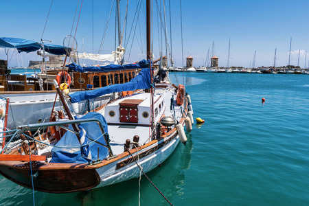 A saling boat moored up in the old harbor of Rhodes. In the distance you can see the three famous windmills