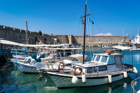 This is a picture of several fishing boats moored in Rhodes harbor in Greece just outside of the old cityu walls