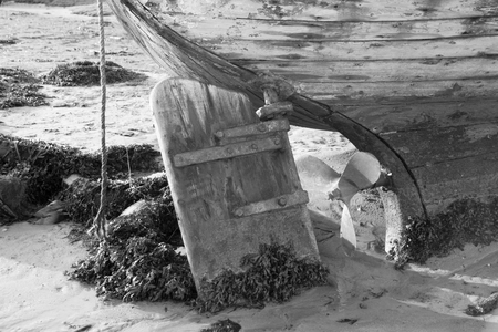 This is a black and white photograph of the rudder of an old beached wooden fishing boat