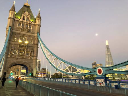 This a picute on hte deck of Tower Bridge in London. It was taken at sunrise. The moon and the London skyline can be seen in the distance.
