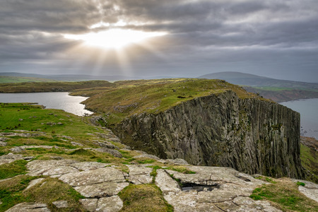A small break in the clouds above Fair Head in North Ireland allows rays of sunshine to illuminated the lake and the cliffs for a short time before the sun disappeared with in the clouds again Banco de Imagens
