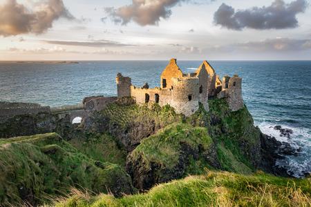 Dies ist ein Bild der Ruinen von Dunluce Castle in Nordirland. Es wurde im 13. Jahrhundert auf einer Klippe mit Blick auf den Atlantischen Ozean erbaut