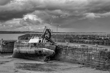 This is an old fishing boat tide up to a pier at low tide.  It is completly out of the water leaning to it side.  It was taken at Burr Point the most easterly point of Northern Ireland