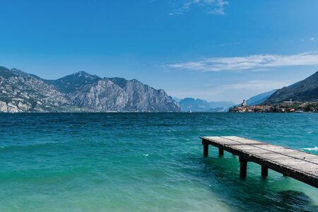 Wooden dock jutting out into the turquosie water of Lake Garda. the village of Malcesine Stock Photo