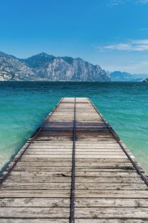Wooden dock jutting out into the turquosie water of Lake Garda Stock Photo